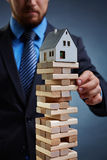 Instability. Businessman touching tower from small wooden blocks with house on its top Stock Images