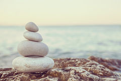 Instagram堆在平静的海滩的石头在日落 免版税库存图片