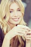 Instagram样式美丽的白肤金发的妇女饮用的咖啡 库存照片