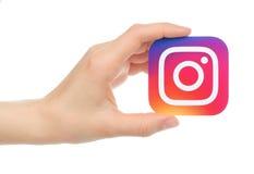 Το χέρι κρατά το νέο λογότυπο Instagram τυπωμένο σε χαρτί