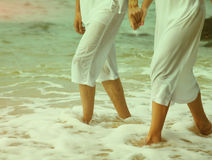 Instagram colorized vintage couple at beach legs portrait. Instagram colorized vintage body part outdoor portrait of couple's legs in white cotton clothes stock images