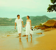 Instagram colorized vintage couple on beach portrait. Instagram colorized vintage outdoor portrait of young romantic couple in white cotton clothes on beach of royalty free stock image