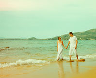 Instagram colorized vintage couple on beach portrait. Instagram colorized vintage outdoor portrait of young romantic couple in white cotton clothes on beach of stock photo
