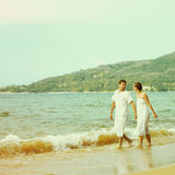 Instagram colorized vintage couple on beach portrait. Instagram colorized vintage outdoor portrait of young romantic couple in white cotton clothes on beach of royalty free stock photos