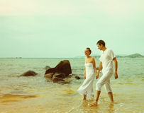 Instagram colorized vintage couple on beach portrait. Instagram colorized vintage outdoor portrait of young romantic couple in white cotton clothes on beach of royalty free stock photography