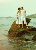 Instagram colorized vintage couple on beach portrait Stock Photos