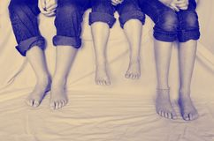 Instagram of Family Legs Bare Feet. Instagrams of family sitting with jeans rolled up sharing fun moment of happiness together bare feet Royalty Free Stock Photos