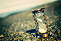 Instagram Hourglass. Sand Timer on Pebble Beach - Hourglass on stony beach, with an instagram effect Stock Image
