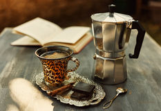 Instagram looking picture of cup of coffee and moka pot. Instagram looking picture of cup of coffee, vintage moka pot, chocolate and cinnamon. Color toned with Royalty Free Stock Photo