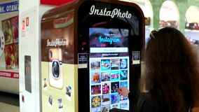 Instagram, the machine to print a photo, a young girl chooses insta foto, the exchange of data via the Internet. stock video footage