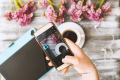 Instagram photographer blogging workshop concept, hand holding phone and taking photo of stylish flowers, cup of coffee. And graphic tablet on grey wooden royalty free stock photo