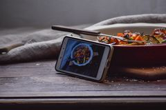 Instagram photography blogging workshop concept. phone near a stylish plate with grilled vegatables on wooden rustic background. Copy space stock photo