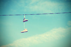 Instagram retro style old shoes hanging on electric cable. Instagram retro style old shoes hanging on an electric cable, old film and vignetting effect royalty free stock photography