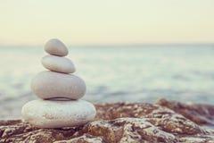 Instagram-Stapel von Steinen auf ruhigem Strand bei Sonnenuntergang lizenzfreie stockbilder