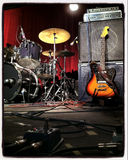 Instagram style image of a guitar and drums on stage. Before a gig Stock Photography