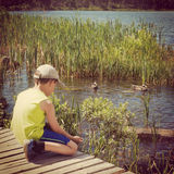 Instagram of young boy feeding ducks  from his hand Royalty Free Stock Images