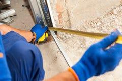 A instalação da porta da garagem Uso do trabalhador uma régua verificar a instalação correta do perfil do metal foto de stock