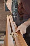 A instalação da porta, instala as dobradiças de bronze para a porta interior de madeira, furo furado carpinteiro, close-up foto de stock