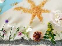 A instalação das flores na argila azul, no céu do papel azul, em um bise em vez das nuvens, no sol do sal alaranjado do mar e em  imagem de stock