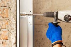 A instalação das portas da garagem O trabalhador fura um furo para o parafuso fotos de stock