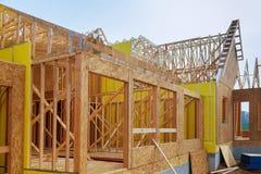 A instalação de feixes de madeira na construção da foto da casa de quadro de uma casa nova sob a construção Fotos de Stock Royalty Free