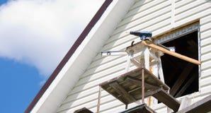 A instalação de um tapume em uma casa contra o céu fotos de stock