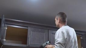 A instalação do carpinteiro da cozinha da guarnição de quadro moldando da coroa no armário vídeos de arquivo