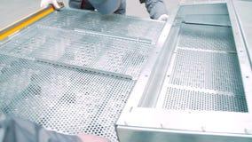 A instalação do equipamento industrial usando as grades de alumínio Trabalhadores na oficina filme