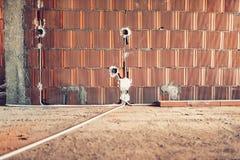 A instalação dos soquetes bondes nas paredes no canteiro de obras da casa fotografia de stock