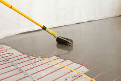A instalação elétrica do sistema de aquecimento de assoalho na casa nova O trabalhador alinha o cimento com o rolo Fotografia de Stock