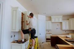 Instalación de la cocina El trabajador instala puertas al armario de cocina imagenes de archivo