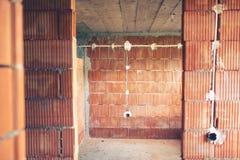 Instalación de los alambres y tubos eléctricos de electricidad en emplazamiento de la obra de la nueva casa Fotos de archivo libres de regalías