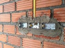 instalación de los zócalos eléctricos en paredes de ladrillo en el constructi de la casa Imágenes de archivo libres de regalías