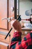 Instalación del carpintero del nuevo tirador de puerta foto de archivo libre de regalías
