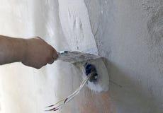 Instalación del enchufe de pared Trabajo sobre la instalación de los mercados eléctricos El electricista prepara los mercados apr imagen de archivo libre de regalías