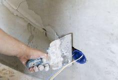 Instalación del enchufe de pared Trabajo sobre la instalación de los mercados eléctricos El electricista prepara los mercados apr foto de archivo
