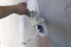 Instalación del enchufe de pared Trabajo sobre la instalación de los mercados eléctricos El electricista prepara los mercados apr fotografía de archivo