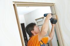 Instalación del marco de puerta El carpintero trabaja con el taladro imágenes de archivo libres de regalías