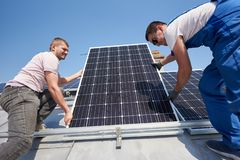 Instalación del sistema fotovoltaico solar del panel en el tejado de la casa foto de archivo