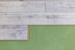 Instalación del suelo laminado La mano instala de piso laminado imágenes de archivo libres de regalías