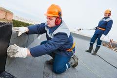 Instalación del tejado plano Fieltro de calefacción y de fusión de la techumbre del betún foto de archivo libre de regalías