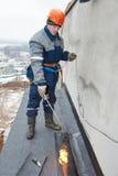 Instalación del tejado plano Trabajadores que derriten el fieltro de la techumbre del betún fotografía de archivo