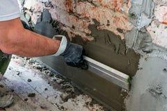Instalaci?n de los faros rectores del metal para llenar y nivelar de paredes en la reparaci?n La mano cubre la pared con yeso fotos de archivo libres de regalías