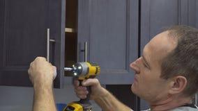 instalaci?n de tiradores de puerta en los armarios de cocina con un destornillador metrajes