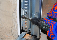 Instalación del panel de la puerta del garaje Hombre que usa el taladro Foto de archivo