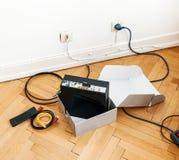 Instalacja kablowy dostawcy internetu modem na drewnianej podłoga wewnątrz zdjęcie stock