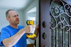 Instalacja wnętrze z kędziorkiem w drzwiowym liściu używać świderu śrubokręt dato che trzymający, śrubuje zdjęcie royalty free