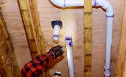 Instalacja wodnokanalizacyjna budynku kontrahent instaluje plastikową rynsztokową drymbę obyczajowy dom fotografia stock