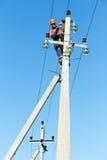 Instalador de líneas del electricista de la potencia en el trabajo sobre polo Fotos de archivo