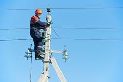 Instalador de líneas del electricista de la potencia en el trabajo sobre poste Fotos de archivo